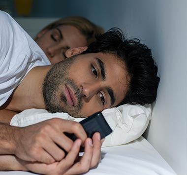 cheater in bed texting